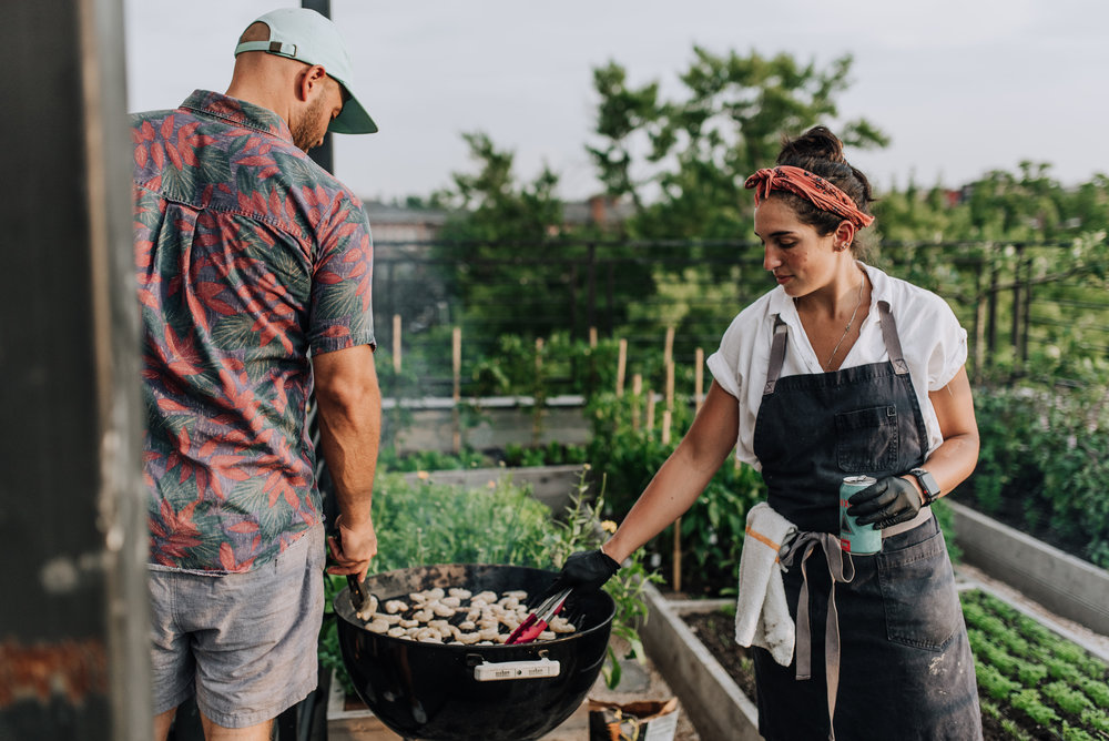 Timber Pizza Co. founder Andrew Dana and Chef Daniela Moreira preparing the meal next to the rooftop garden.