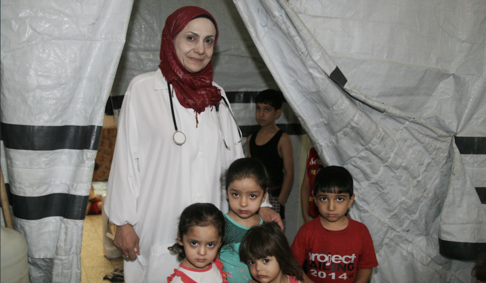 Dr. Sana'a, a mother and a doctor, listens to her patients of all ages at the UNRWA Damascus Training Centre collective shelter, Syria