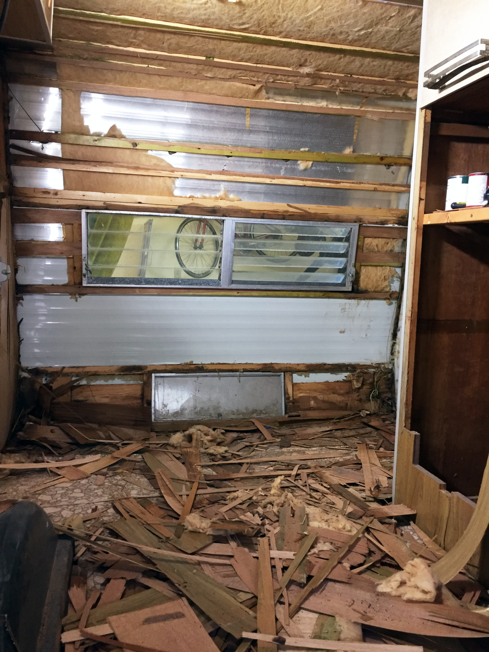 All of those paper-thin wood shards on the ground used to make up the back and side walls of the camper. But look at that cute little metal hatch to the exterior of the camper at the bottom of the wall! We've got some ideas for that later.