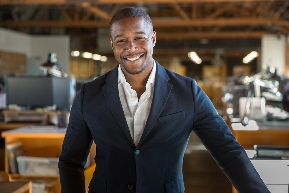 Charming successful smiling portrait of handsome african american professional in suit at office.jpg