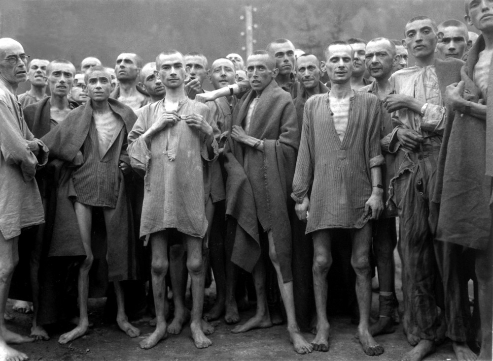 "Starved prisoners, nearly dead from hunger, pose in concentration camp in Ebensee, Austria. The camp was reputedly used for ""scientific"" experiments. It was liberated by the 80th Division. May 7, 1945. Lt. A. E. Samuelson. (Army) NARA FILE #: 111-SC-204480 WAR & CONFLICT BOOK #: 1103"