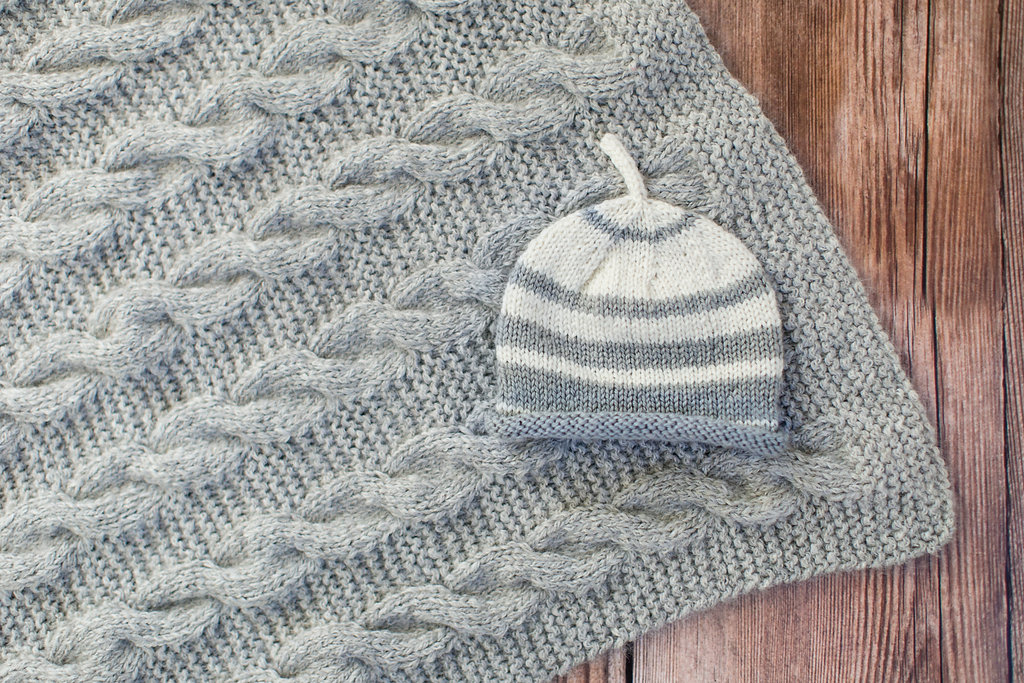 My striped baby hat- a soak wash kit- on a gorgeous alpaca bamboo (Classic Elite Chalet) cable blanket knit by Finch Teacher, Cassie.