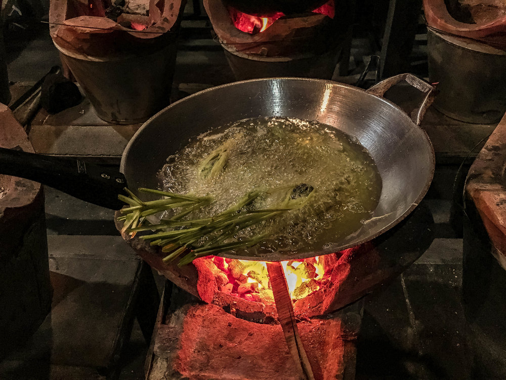 ONCE STUFFED, THE LEMONGRASS IS FRIED OVER A FIRE IN A SKILLET