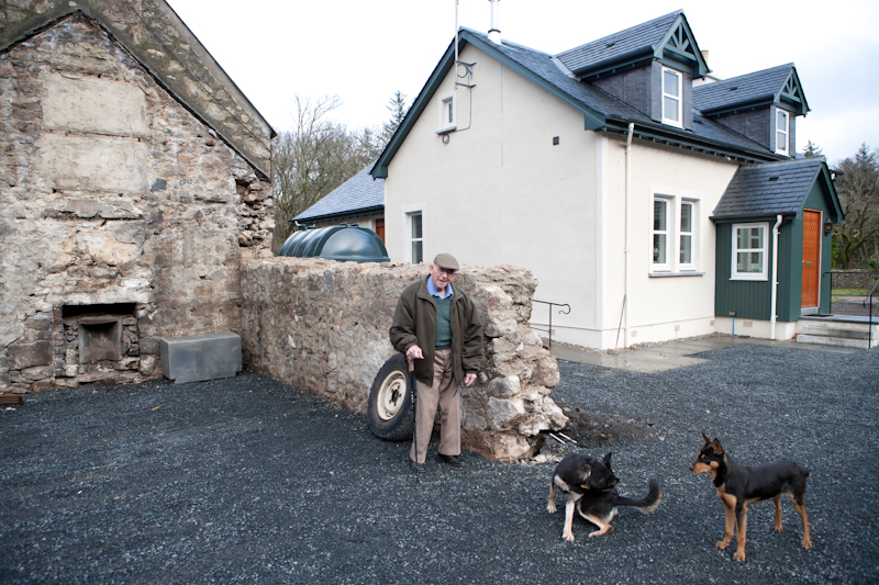 Lachie with the old cottage site and the new cottage behind. © John MacPherson