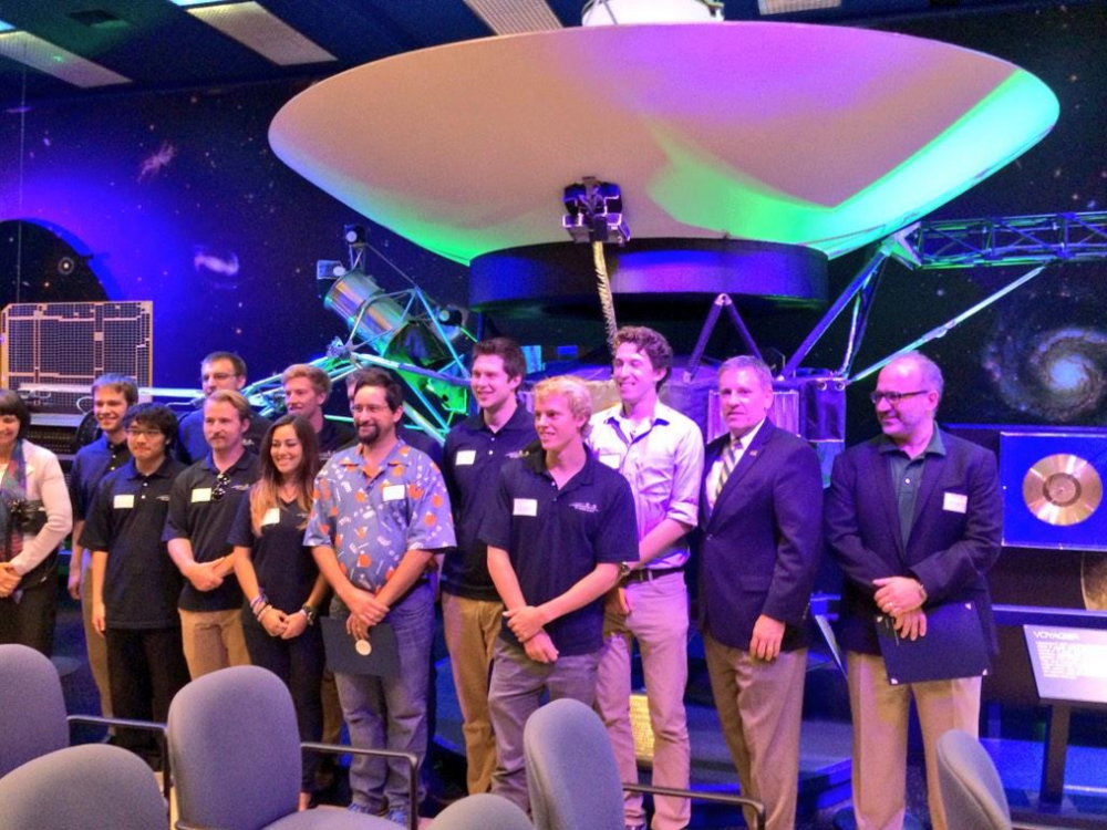 Cal Poly's President Jeffrey Armstrong and the Dean of Engineering Debra Larson with the PolySat and CubeSat team in front of Voyager at JPL.