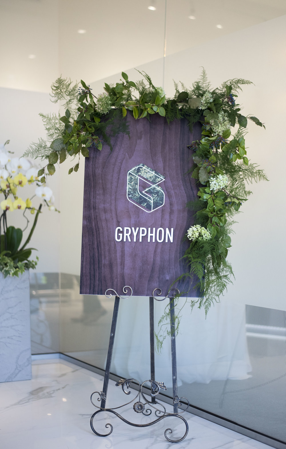 A beautiful vintage easel housed a custom greeting sign decorated with elegant greenery.