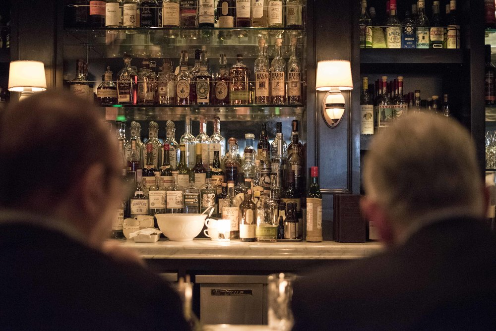 Two gentlemen enjoy their dinner at the bar.