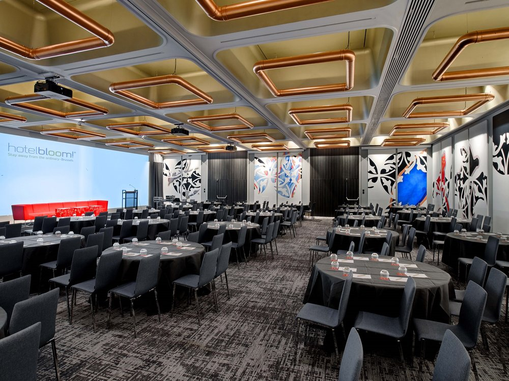 Bright, bold graphics adorn the conference room wall panels and lighting pieces share a similar aesthetic.