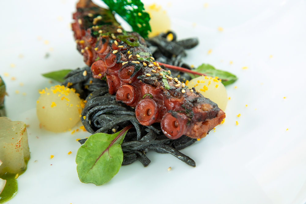 Grilled octopus tentacle on handmade squid ink soba