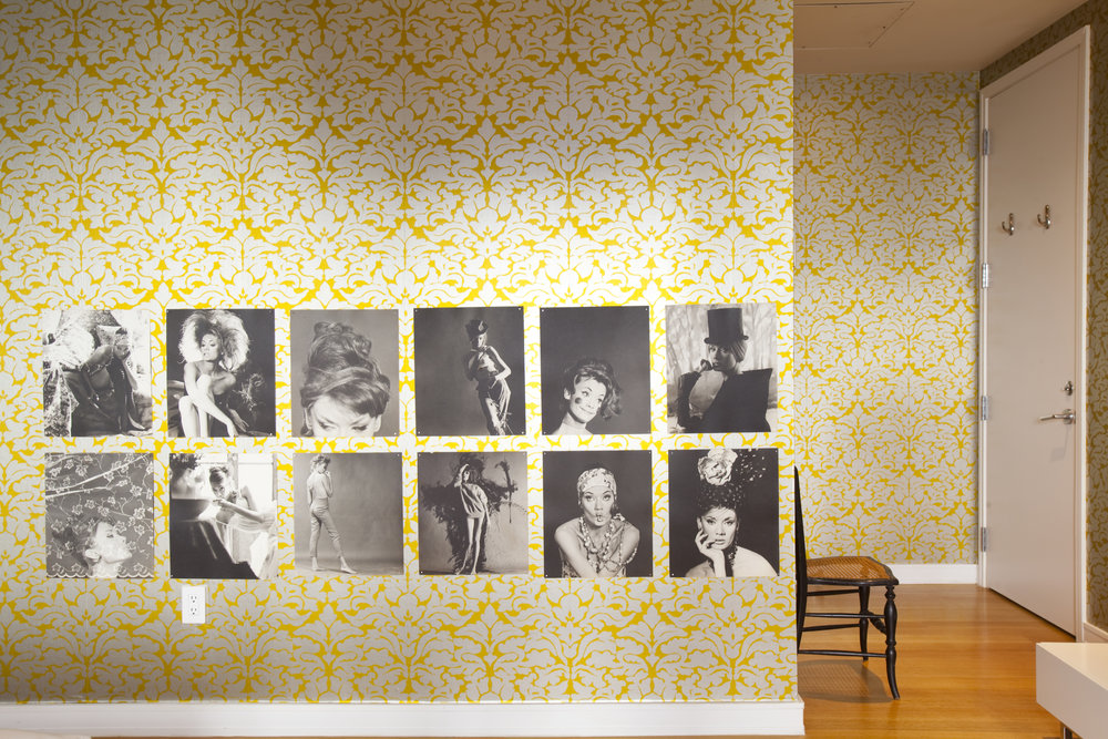 Black and white photos of burlesque dancers line the wall in the master bedroom.