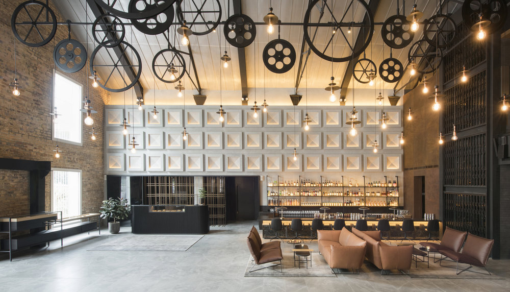 Intricate and vintage machinery wheels act as decorative accents in the hotel lobby.