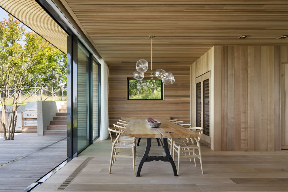 The indoor dining area opens up to an outdoor dining terrace with the sliding door.