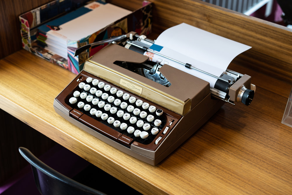 Vintage typewriter station in the lobby with branded Hotel Zed paper.