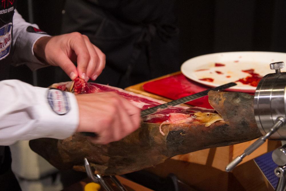 Hand carving Iberico prosciutto.