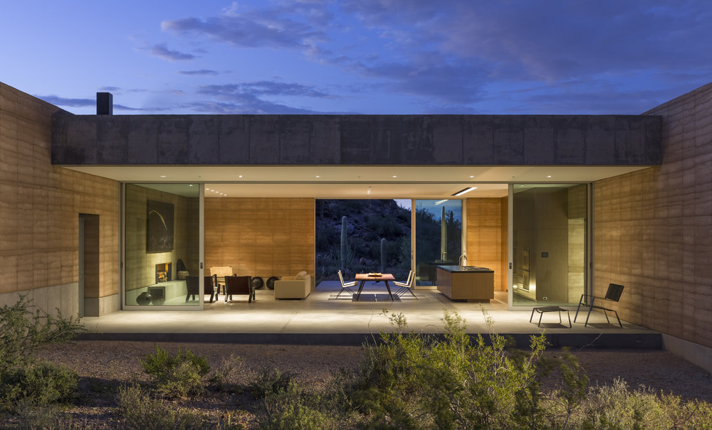 The living room area with a shifting glass wall for a panoramic view of the desert landscape.
