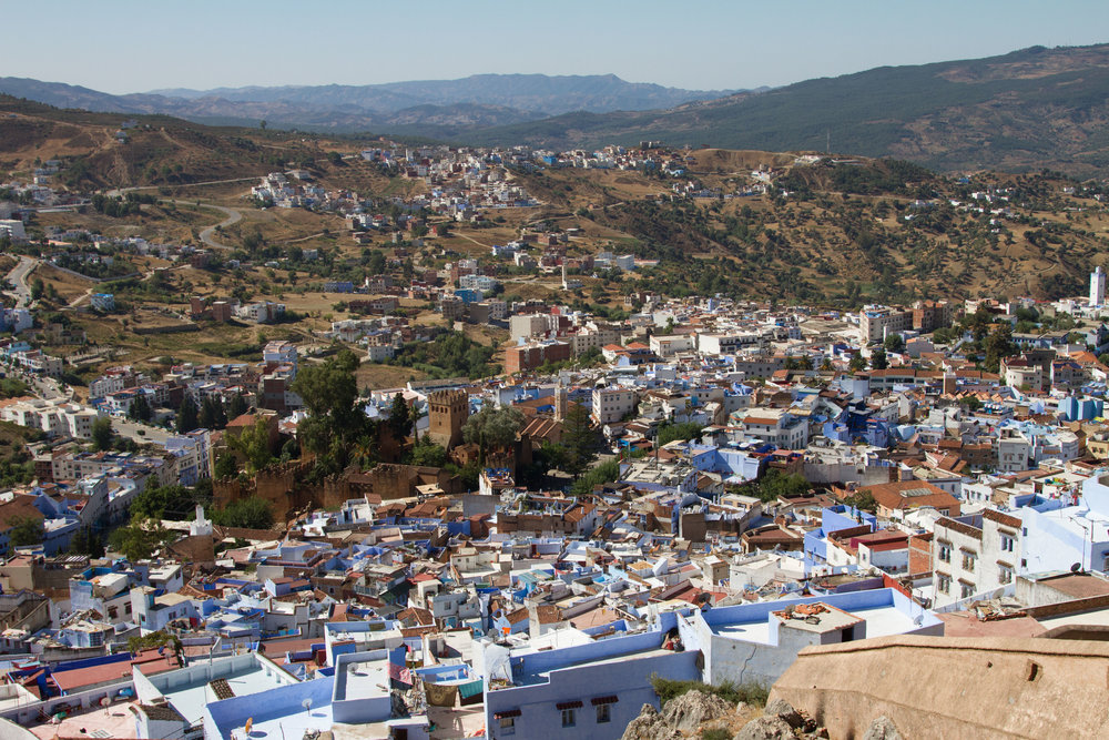 A view of the blue-clad medina of Chefchaouen atop a nearby mountain