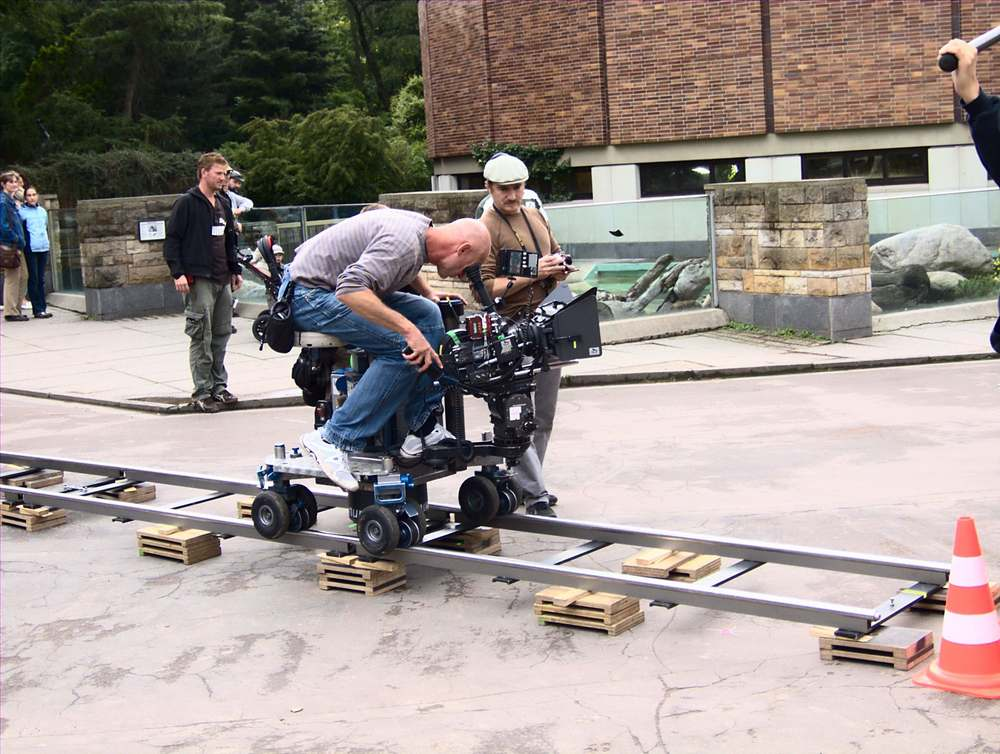 A camera dolly in action. The platform with wheels is placed on a track and can move smoothly back and forth.