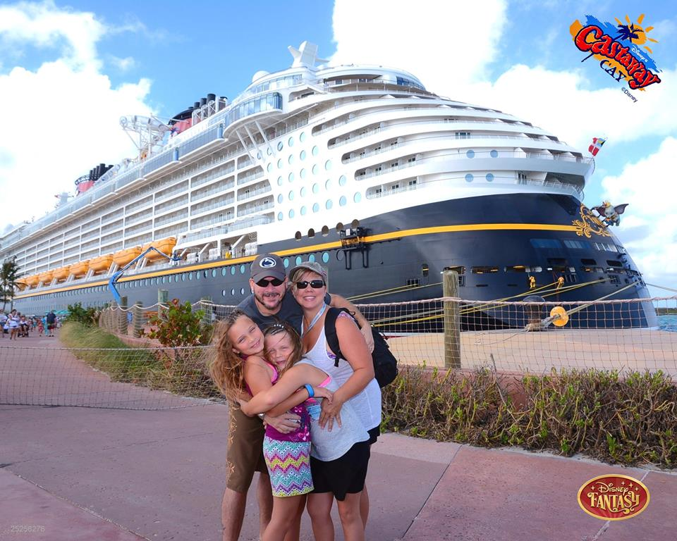 Cara D. and her family on  Disney Castaway Cay, in front of the Disney Fantasy
