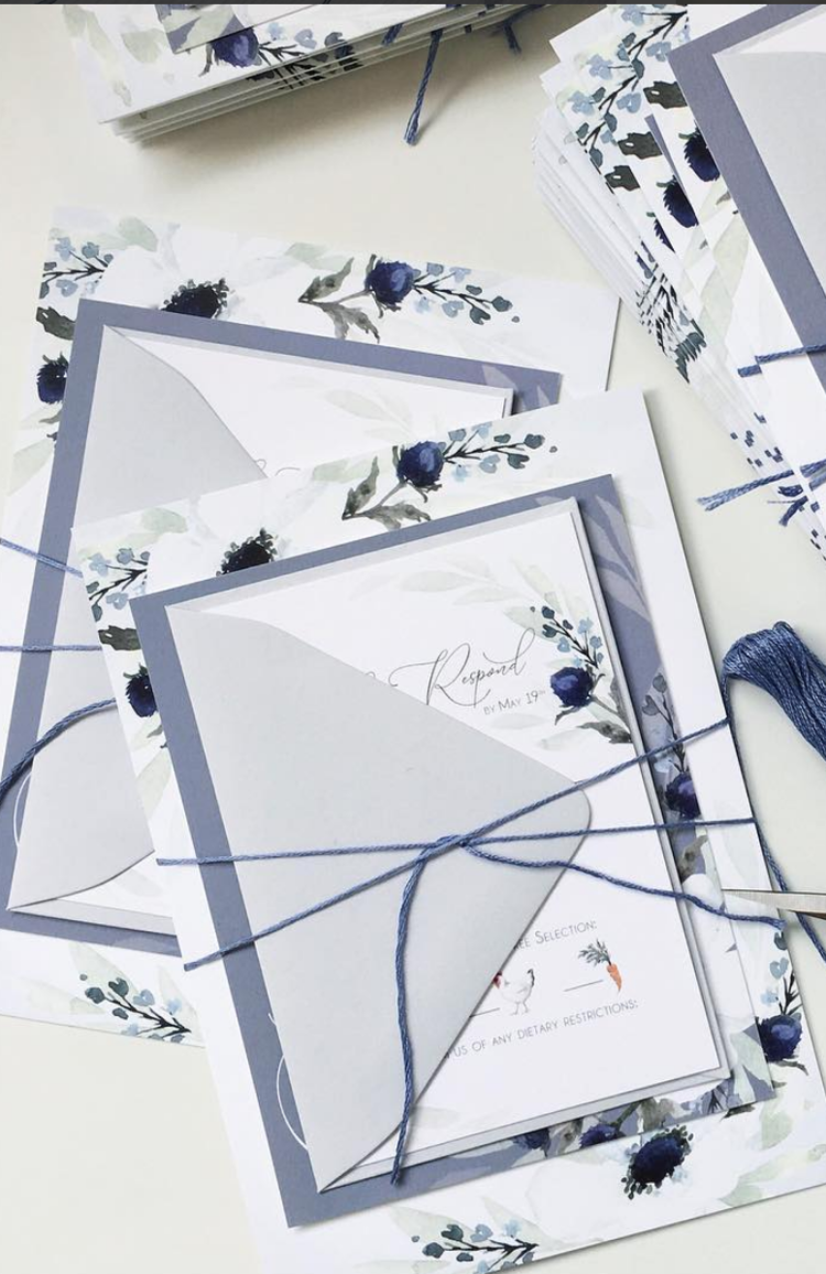 Assembly of Wedding Invitations. French blue wedding invitations with navy thread wrapped around the suite, preparing to be sent out to guests.  Artwork, assembly and photo by Blushed Design, Wedding Invitations and Bridal Portraits