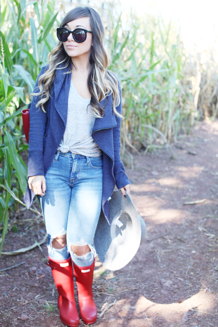 Fashion, lifestyle, and beauty blogger Little Tree Vintage styles ripped denim, red Hunter boots, and a drape jacket for Fall.