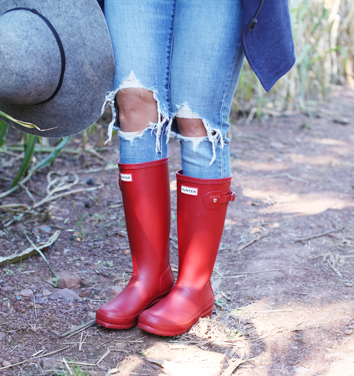 Ripped denim + red Hunter boots styled for Fall from fashion, lifestyle, and beauty blogger Little Tree Vintage.