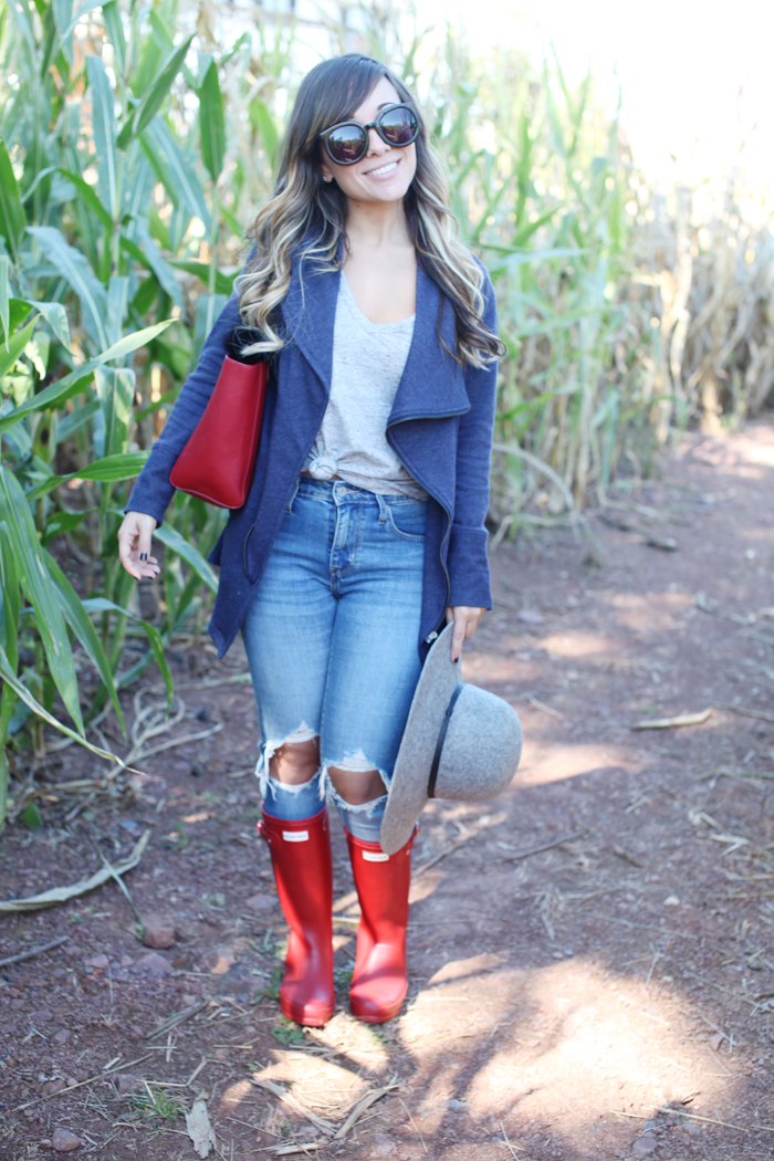 Styling red Hunter boots, ripped denim, and a drape jacket for Fall.