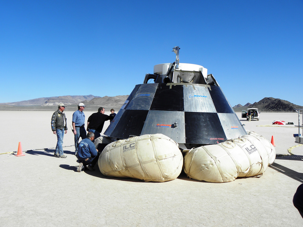 Engineers inspect a drop-test capsule. The test was to validate the airbag landing system. Photo Credit: Boeing
