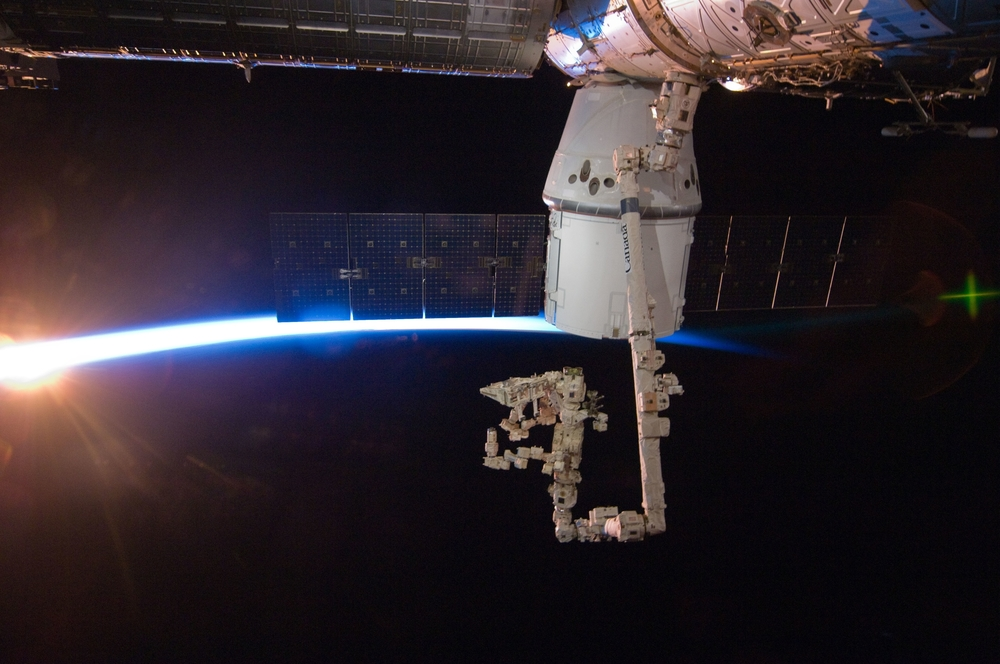 The space station passes into an orbital sunrise with Dragon berthed to the  Harmony  module. Photo Credit: NASA
