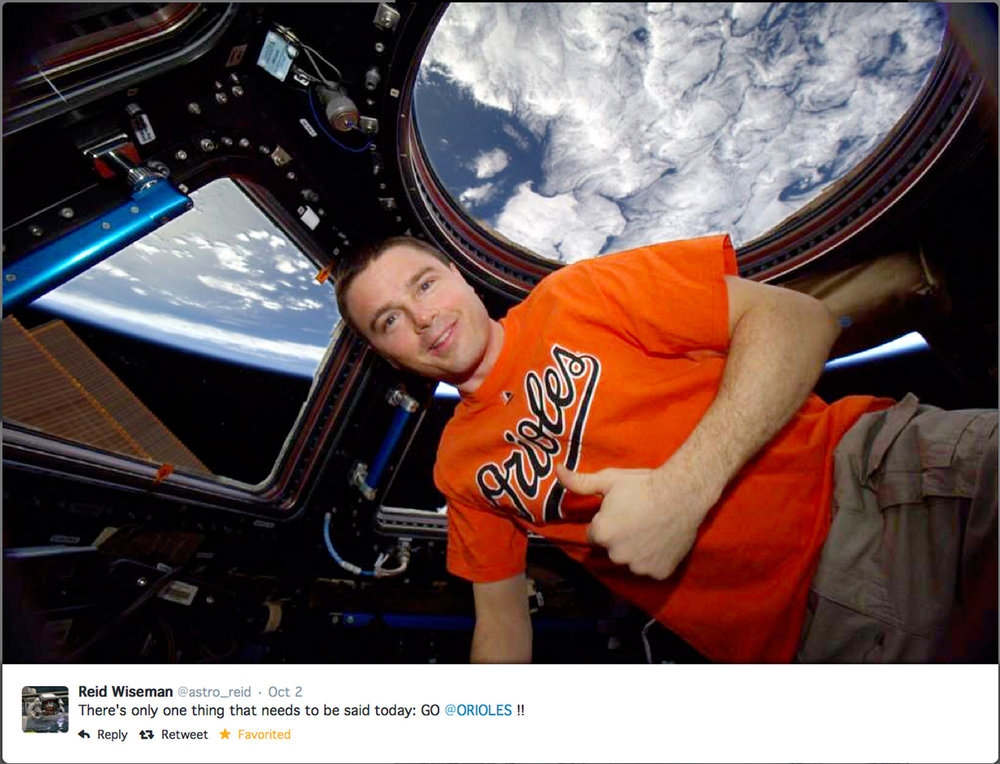 Reid Wiseman inside the International Space Station's cupola window showing support for his favorite baseball team. Photo Credit: NASA