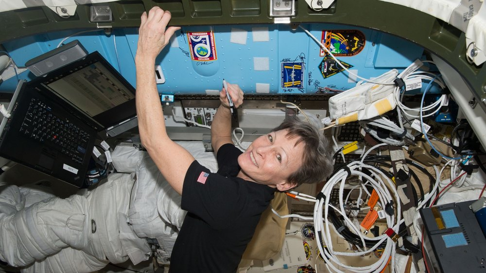 Peggy Whitson signs her name on the wall of the ISS next to an Expedition 50 patch sticker. Whitson, now the commander of the ISS, has surpassed Jeff Williams to become NASA's most experienced astronaut. Photo Credit: NASA