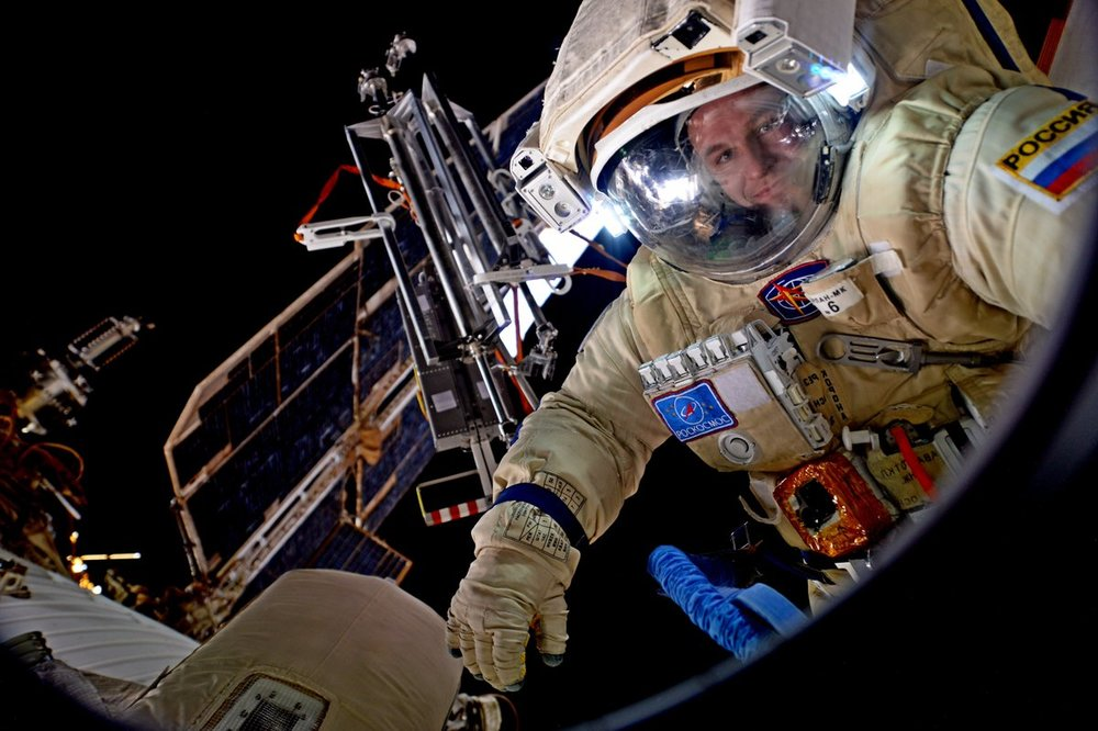 Sergey Ryazanskiy as seen through a window on the Russian side of the space station. Photo Credit: Roscosmos