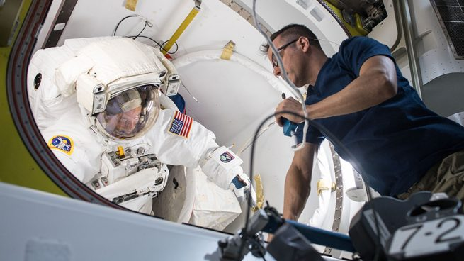 NASA astronaut Joe Acaba works to fit-check Scott Tingle's spacesuit before U.S. EVA-47. Credit: NASA