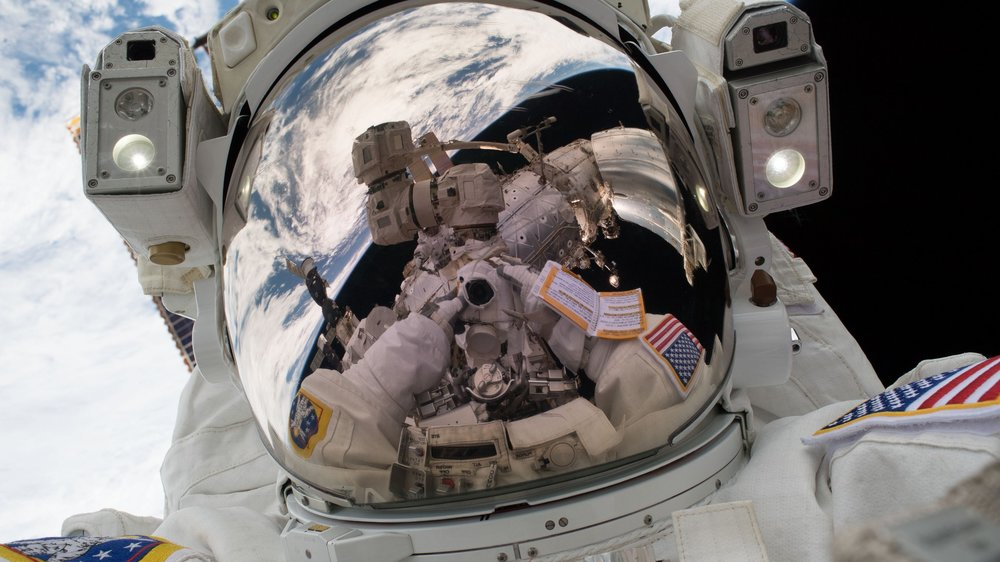 "NASA astronaut Mark Vande Hei takes a ""space-selfie"" during U.S. EVA-47, the first spacewalk of 2018. He once again ventured outside, this time with Japanese astronaut Norishige Kanai, for U.S. EVA-48, which completed work upgrading the robotic Canadarm2. Credit: Mark Vande Hei / NASA"