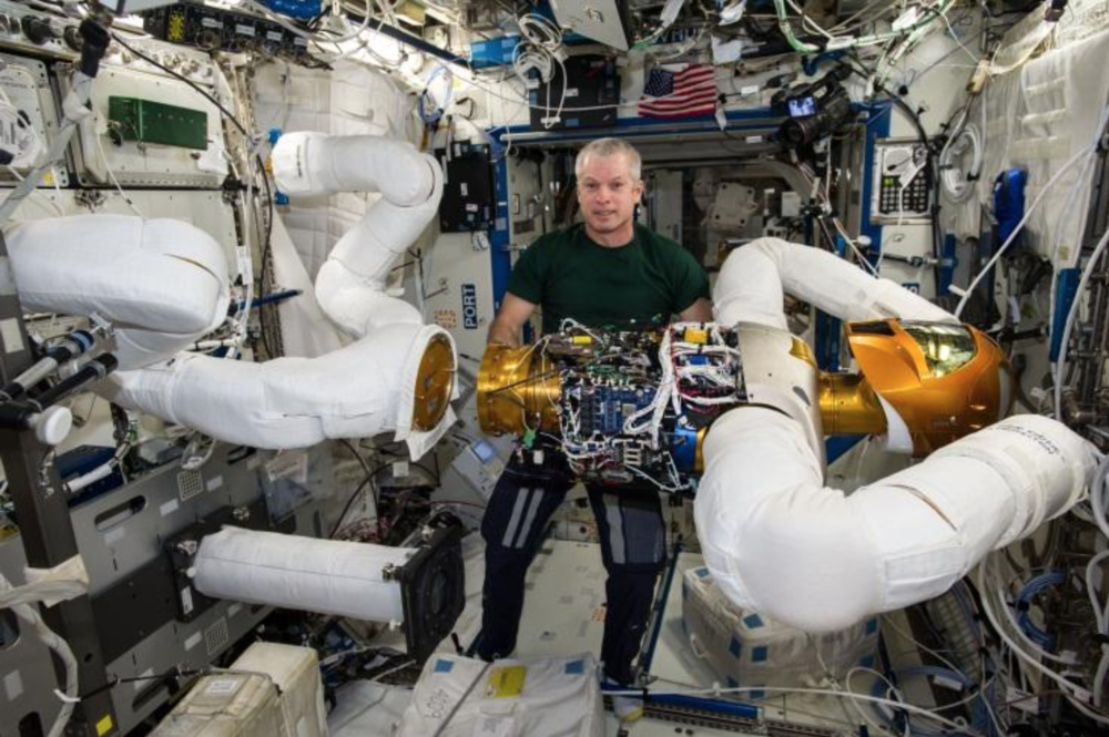 "Expedition 40 commander Steve Swanson performs ""robot surgery"" in a very complex on-orbit upgrade of Robonaut2 during the summer of 2014. Credit: NASA"