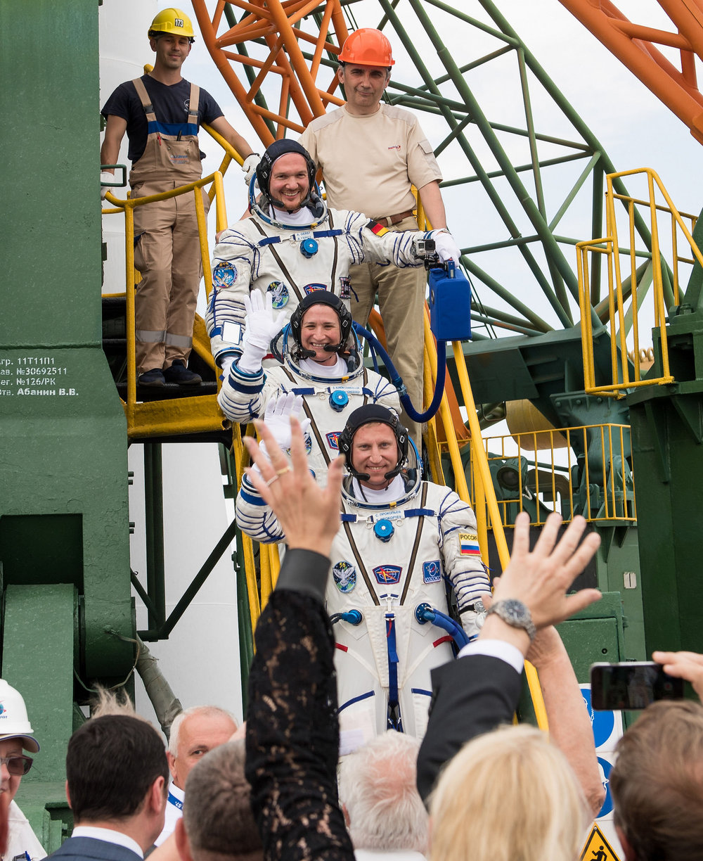 Alexander Gerst of ESA, top, Serena Auñón-Chancellor of NASA, middle, and Soyuz Commander Sergey Prokopyev of Roscosmos wave farewell before boarding the Soyuz MS-09 spacecraft for launch. Credit: Joel Kowsky / NASA