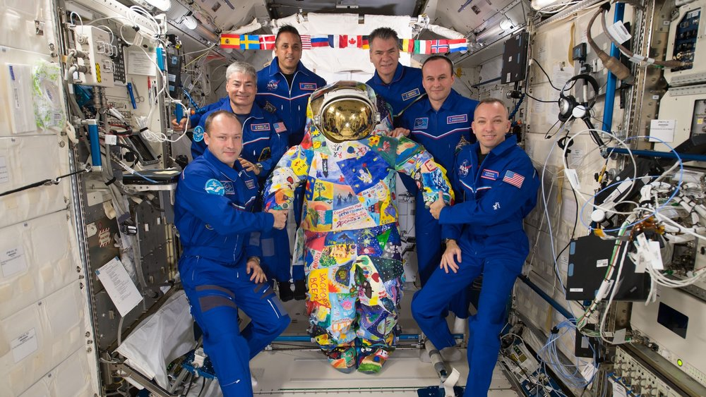 "The Expedition 53 crew hold the ""VICTORY"" art spacesuit, which was hand-painted by cancer patients in Russia and the United States and sent to the ISS via a cargo spacecraft. Credit: NASA"