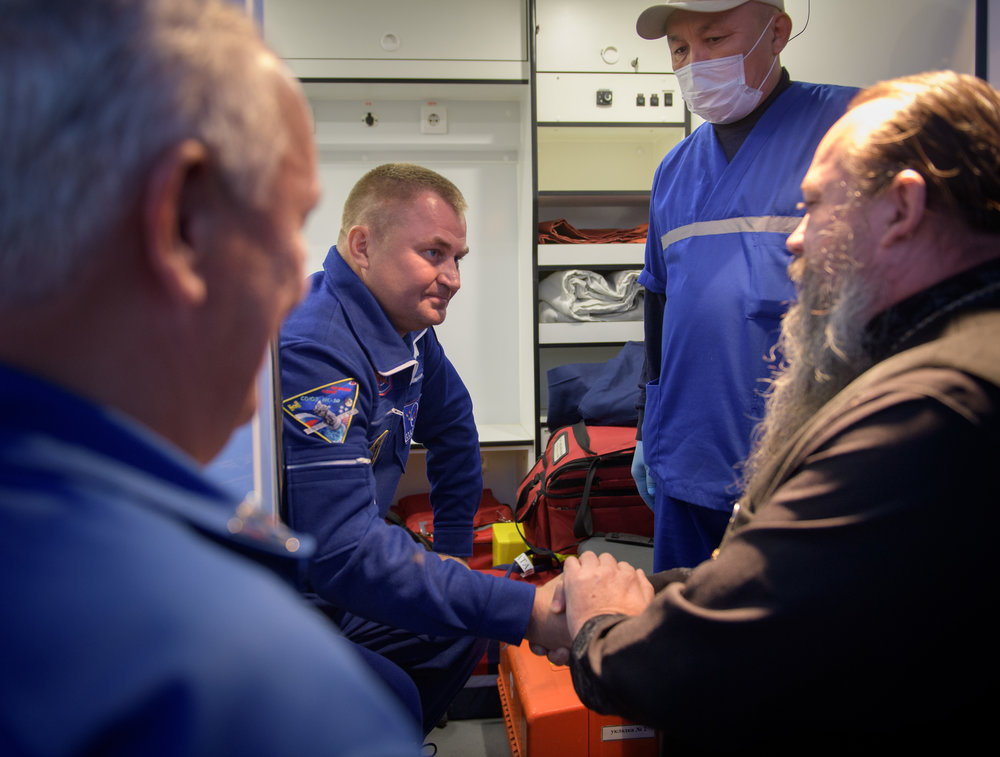 A Russian Orthodox Priest welcomes Aleksey Ovchinin's hand after the Soyuz MS-10 in-flight launch abort. Credit: NASA/Bill Ingalls