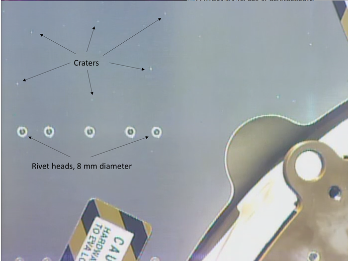 A size comparison of the impacts compared to rivet heads on the Columbus module. Credit: ESA/NASA