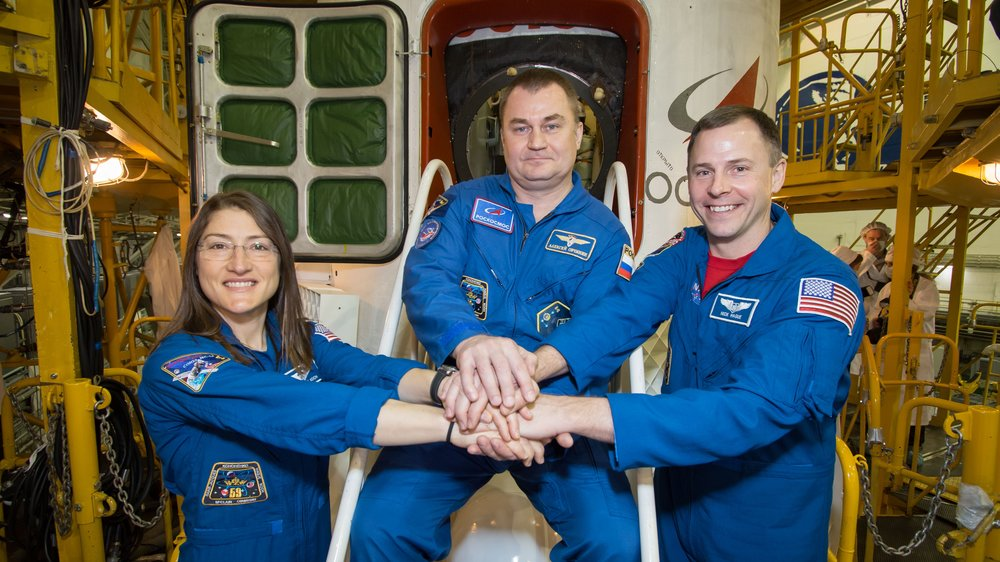 NASA astronaut Christina Koch, left, Russian cosmonaut Aleksey Ovchinin, center, and NASA astronaut Nick Hague stand pose for a photo in front of their Soyuz MS-12 capsule during pre-flight inspections on March 10. Credit: NASA/Victor Zelentsov