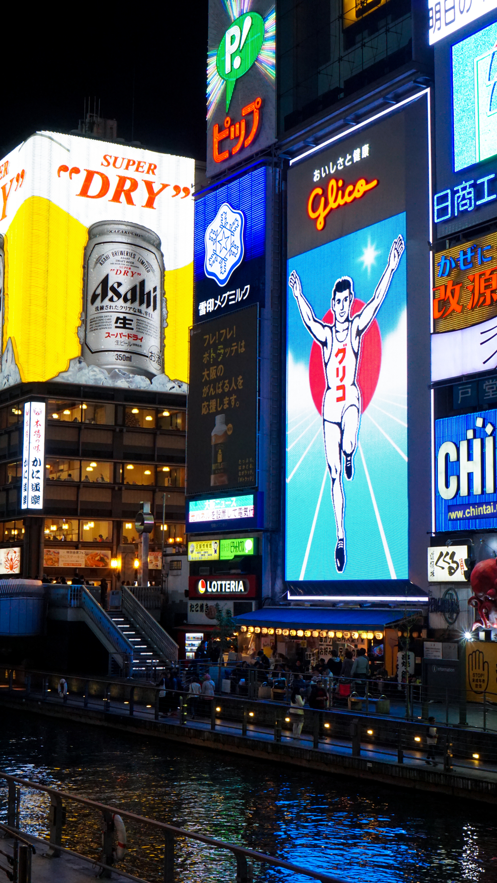 Dotonbori, a famous tourist destination in Osaka, as marked by the evident Glico Running Man sign and unmistakable energy and delicious smell of fried food.