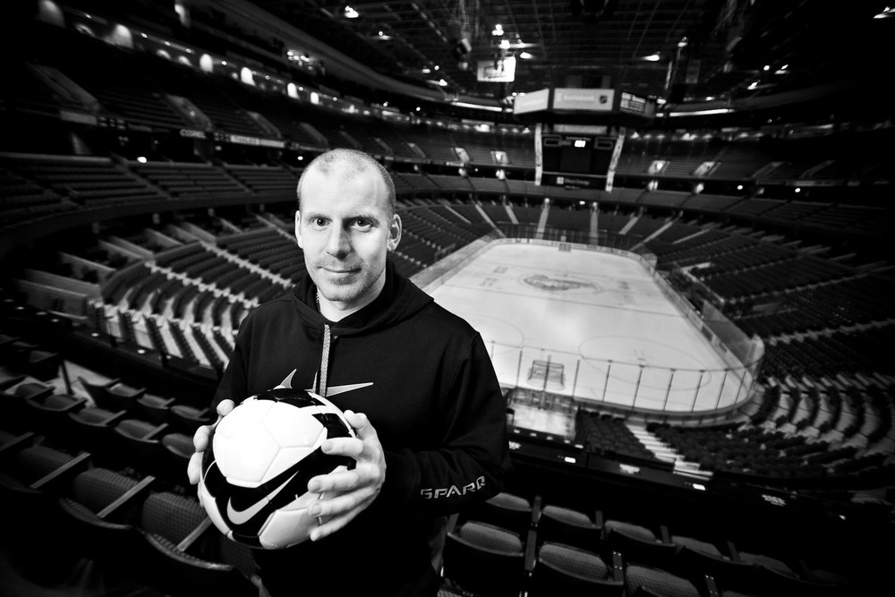 Portrait of a man holding a soccer ball in front of a hockey rink