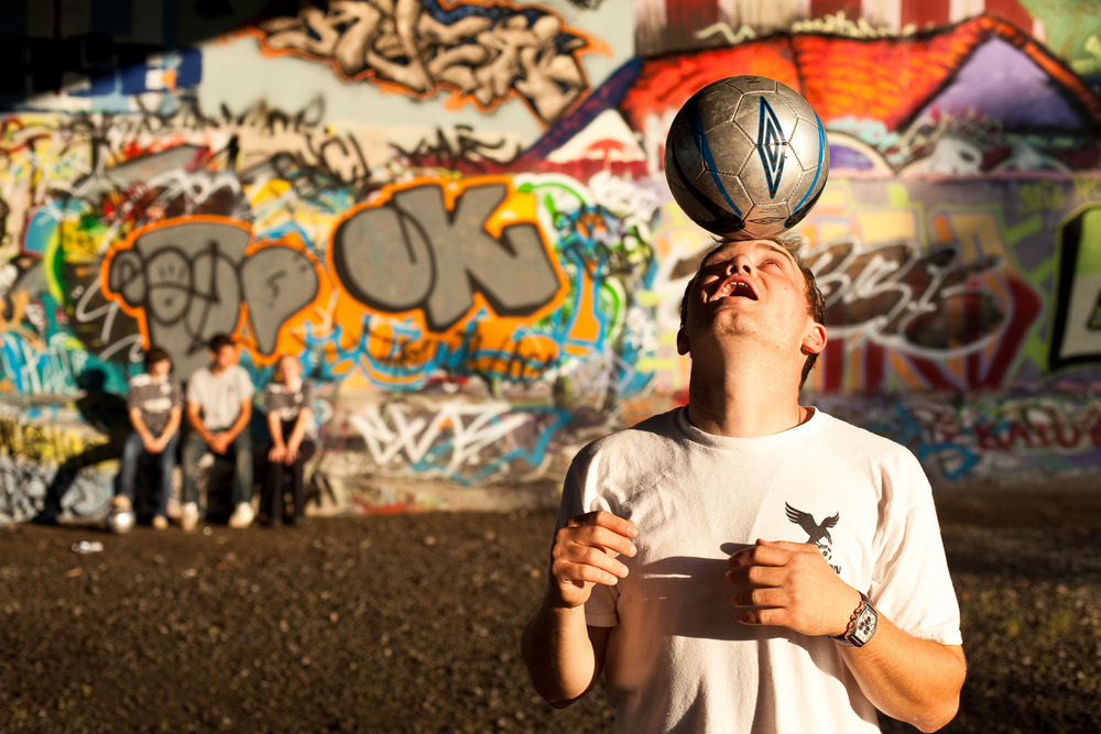 Portrait of a man with a soccer ball under Bronson Bridge