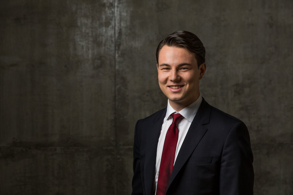 Professional business attire headshot of male on stone background.