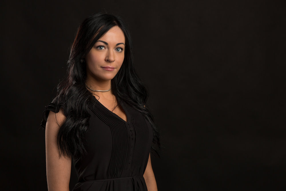Headshot on a black backdrop of a female professional