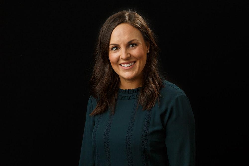 headshot of a woman on a black backdrop