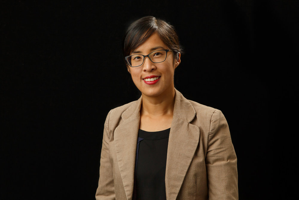 headshot of an asian woman on a black backdrop