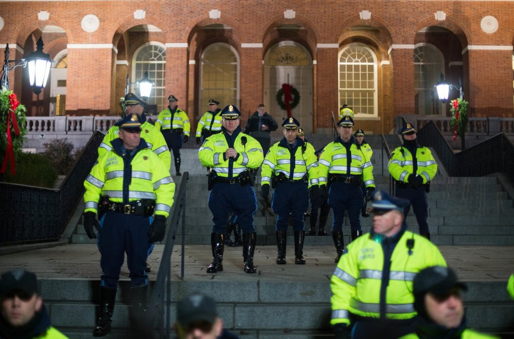 Boston and State police stand behind the Massachusetts State House gates as hundreds gather outside the state house demanding justice for Eric Garner, a black man who died due to a chokehold by a white police officer in State Island in July. Photo By Pankaj Khadka