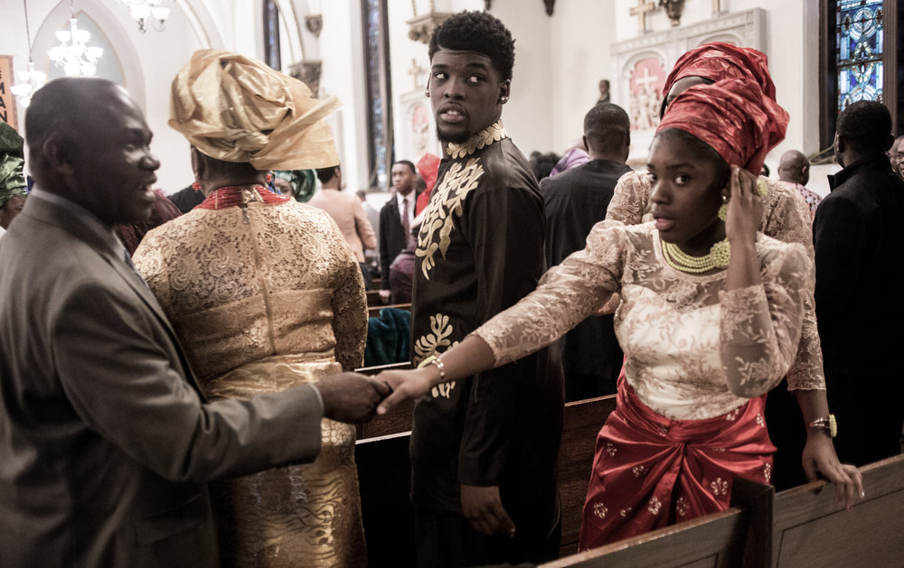 Church attendees greet each other during a Sunday mass on the day of Nigerian Harvest Mass at a church in Mattapan, MA. Photo by Pankaj Khadka