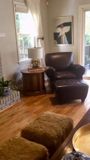 Another un-styled and unedited photo of the space.   Leather chair ottoman... goodbye.  Needing a rug, and some color!