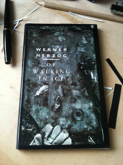 'Books for Photographers that aren't about Photography #2' 'Of Walking in Ice' by Werner Herzog (Munich - Paris. 23rd November-14th December 1974) — I have a pretty bad memory, so at first I couldn't remember where I found my copy of 'Of Walking in Ice' (shown here). Luckily on the inside cover I had written 'winter. Scotland 2000'. Which narrows it down. In the summer of 2000 I had graduated from Brighton University. On a whim and with an invite from an old school friend, I had abandoned the south coast and moved to Edinburgh, or to be precise my friends rather isolated house near Dalkeith. By the Winter, the time of this book purchase, I was living in a small flat in Portobello, Edinburgh. I would explore this area with a camera loaded with black & white film that I couldn't afford to develop; I was making photographs I wouldn't actually see for over a year. Walking was at the heart of this process, my work stemmed from the wandering, minor explorations in the cold Scottish semi-rural hinterland. Its no wonder I was drawn to Herzog's book. 'Of Walking in Ice' is a record of a winter journey made by Werner Herzog in 1974. On hearing that a friend, living in the outskirts of Paris, is very ill he sets off on foot to visit her. He believes that the sheer effort of making this journey on foot will 'bring her back' to health. He sets off from Munich and heads cross country to Paris, a journey that will take him three months, with little else but a map, compass and a few things in a duffel bag. He skirts the black forest, walks the Rhien and the Seine; Paris takes shape gradually as he walks into the city through its edges. He takes shelter where he can, sometimes using barns or abandoned houses in which to sleep. The weather becomes a central character of the book, thick damp fog, cold sharp rain and of course snow fill the pages. After a day or two, away from people, and open to the elements Herzog enters a kind of reverie, he observes the landscape in beautiful detail, with a seemingly fresh clarity.Although Herzog is obviously a romantic, this isn't an idealistic stroll through Arcadia. The reality of the journey ahead cuts in with the pain of blisters, the discomfort of sleeping rough and the momentary feeling of the ridiculousness of the task he has taken on. The landscape of his writing is often a clash of the natural and the artificial, he notices that even in this modern wilderness you are never far away from rubbish, litter and abandoned vehicles. One of the reasons I recommend this book to photographers is because of the way Herzog observes and describes tiny visual details so well. Herzog's reverie, his wandering and his observations, felt like my experience in the winter landscape of Scotland at this time. In his momentary doubts of the sanity of what he was doing, I also recognised something of what I felt about my picture making: why was I going out, making pictures that no one was interested in, that I couldn't afford to even develop and look at? These are probably familiar feelings for many photographers. During my winter in Scotland I found Werner Herzog's beautifully visual & romantic journey a comfort, something familiar to come back to after exploring a winter hinterland of my own. Its belief in the journey as an action of creativity also helped me while I asked a lot of questions about my work, and why I made it. – 'Of Walking in Ice' is a lovely book of just under 90 pages. I'm sure I probably found my copy in one of Edinburgh's second hand book shops for a pound or two, but looking on line it looks like its now going for about £20. I still think its worth every penny. (via Amazon UK) (via Amazon USA) (via Abe Books)